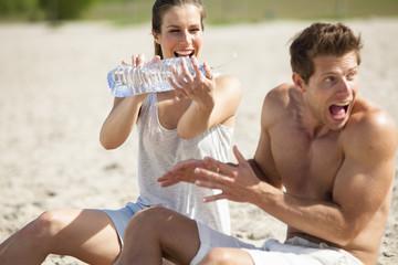 Paare bespritzt sich mit Flasche Wasser am Strand