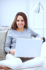 Happy pretty woman using laptop sitting on  sofa