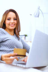 Beautiful smiling woman with laptop and a credit card