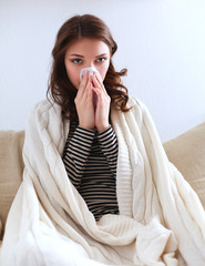 Portrait of a sick woman blowing her nose while sitting on the