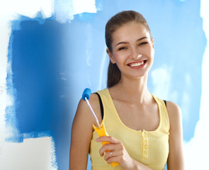 Happy beautiful young woman doing wall painting,