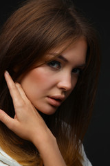 Portrait of beautiful young woman face. Isolated on dark