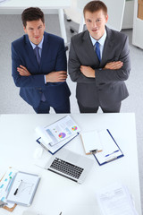 Two businessmen standing with a blank sheet of paper