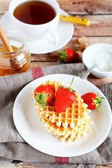 Waffles with strawberries and sweet black tea