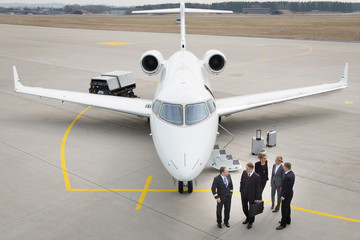 executive business team in front of corporate jet talking to pil