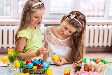 Children paint Easter eggs at home.