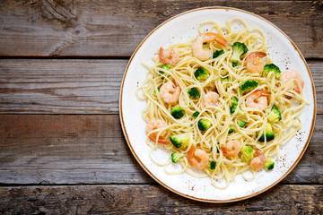 Pasta with broccoli and prawns on a plate on a wooden background