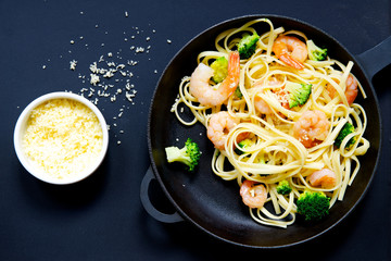 Pasta with prawns and broccoli in a frying pan
