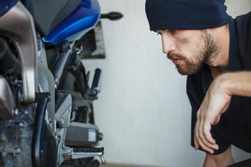 Serious young man repairing his motorcycle in garage