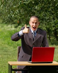 man with red laptop working outdoors