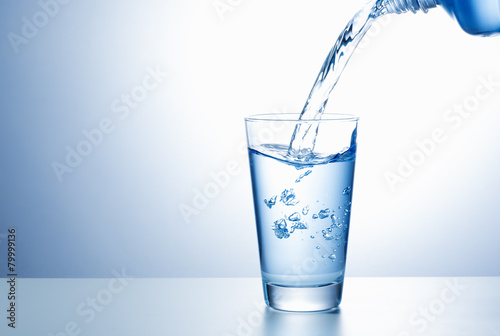 Pouring water from bottle into glass - 79999136
