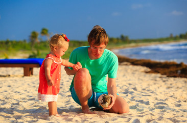 father and little daughter looking at coconut on the beach
