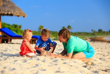 father and two kids playing with sand on beach