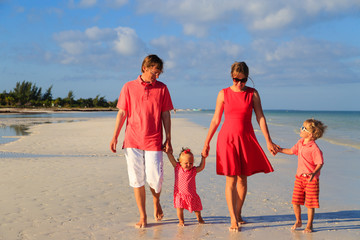 Young family with two kids walking at the beach
