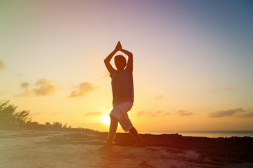 Silhouette of young man doing yoga at sunset