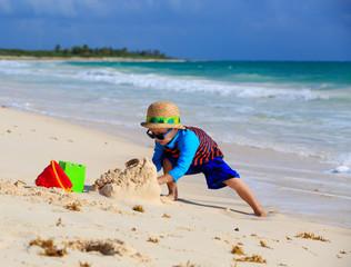 little boy building sandcastle on the beach