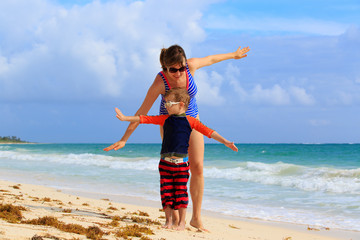 mother and son flying on the beach