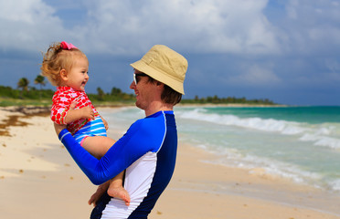 happy father and little daughter on the beach