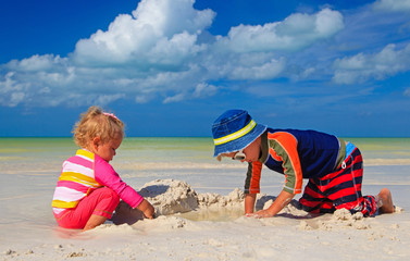 little boy and toddler girl building sandcastle on the beach