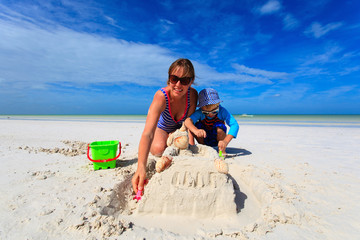 mother and son building sand castle on summer beach