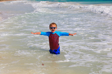 happy little boy playing in waves at beach