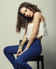Young fashion model sitting on chair