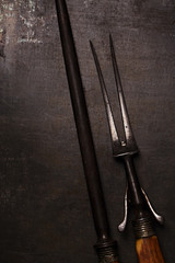 stylish vintage meat fork and sharpener on metal backdrop