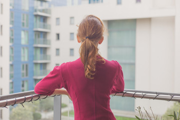 Woman standing on balcony of apartment