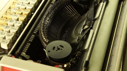 Vintage typewriter rotates on a black background loop