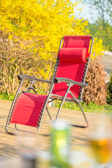 Folding red chair on backyard patio