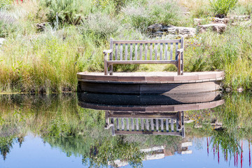 Bench on Shore of Lake with Reflection