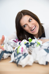 Angry businesswoman sitting at the table with trash paper