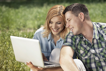 Cheerful young couple sitting on the grass, looking at laptop an
