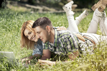 Happy young couple lying on the grass, looking at laptop and smi