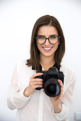 Cheerful young businesswoman in glasses holding camera