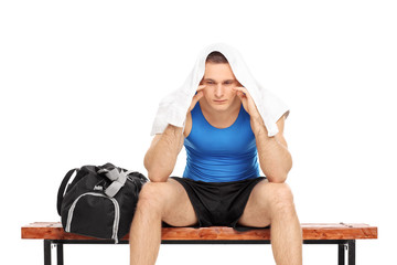 Worried male sportsman sitting on a bench
