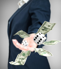 Close up of businessman throwing dice and dollars. Gambling conc
