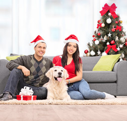 Young couple celebrating Christmas with their dog