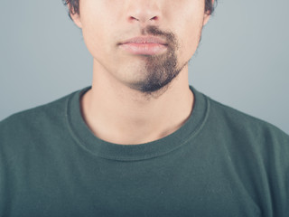 Young man with half shaved beard