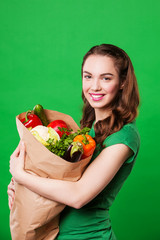 beautiful woman holding a grocery bag full of fresh and healthy