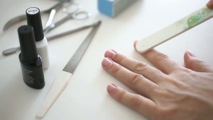 female hands doing manicure, sawing nails nail file. HD