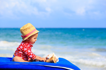 cute little girl  with seashells on the beach