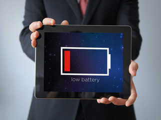 businessman with low battery tablet