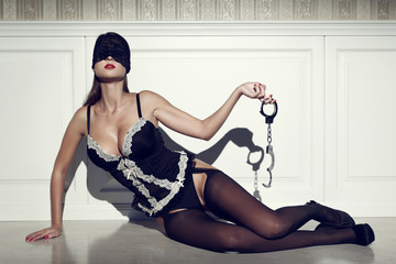 Sexy woman with lace eye cover and handcuffs