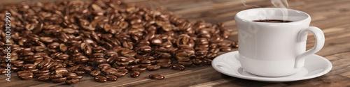 Leinwandbild Motiv Frische Tasse Kaffee mit vielen Kaffeebohnen