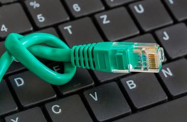Netzwerkkabel grün mit Knoten und Tastatur