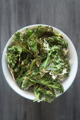 Homemade Curly Kale Chips Sprinkled with Parmesan Cheese