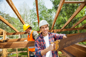Happy Worker Cutting Wood With Handsaw At Construction Site