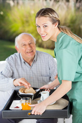 Portrait Of Smiling Female Nurse Serving Breakfast To Senior Man