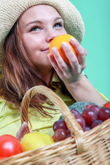 Young woman holding a basket full of healthy food